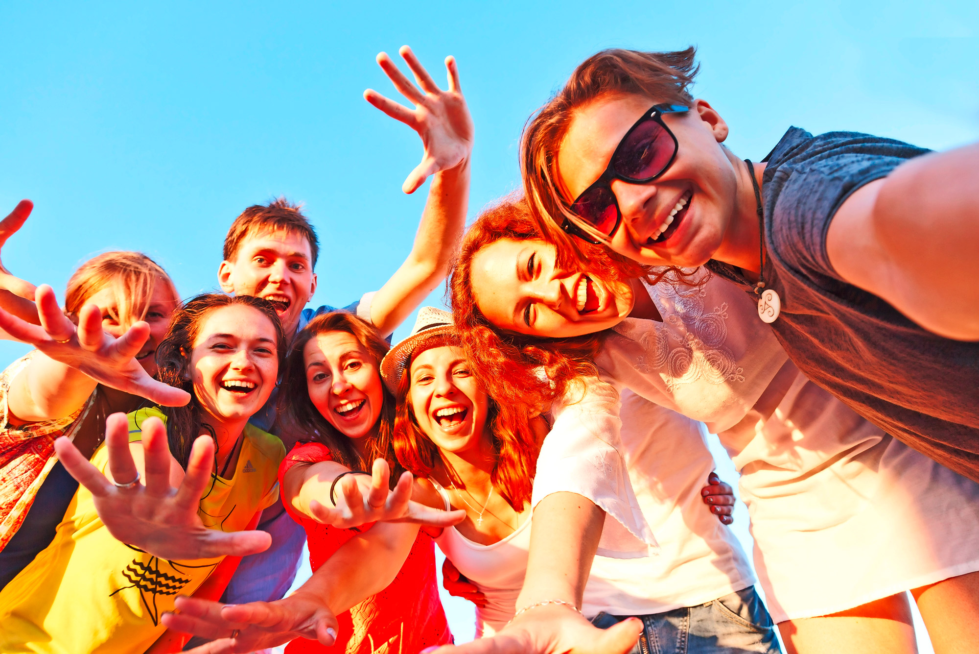 Group of happy young friends doing selfie against the blue sky. Friendship day, companionship, happiness.
